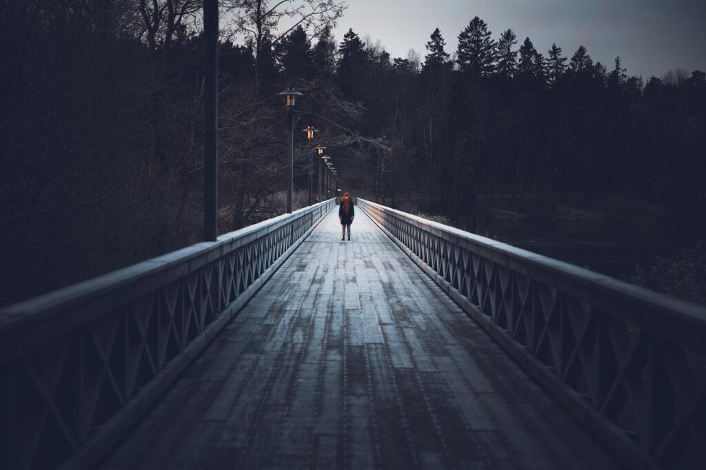 En kvinna står på mitten av en lång bro precis innan solen har gått upp.