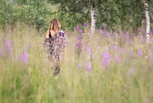 Laila går på sommaräng med blommor och björkar.